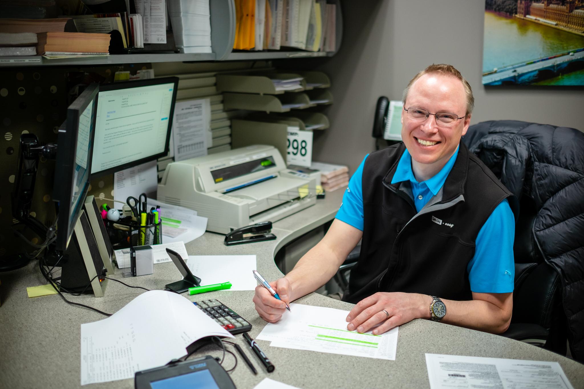 Man smiling doing paperwork